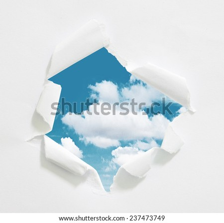 Round hole in paper with sky background inside