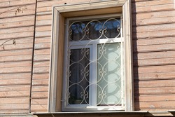 Round iron bars on the windows in a wooden house. Window protection.