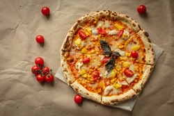 Round large pizza with tomatoes, pineapple, corn, chicken, sauce, cheese. Kraft paper and wooden tray.
