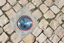 Round led lamp for night illumination of buildings and objects , with a metal rim and durable tempered glass, built into the stone surface of the sidewalk pedestrian zone