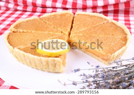 Round lemon cake, cut into slices. Delicious lemon cake. Pastries, patisserie, cafeteria. Pie and lemon. Dried lavender and pie on the table. Selective Focus.
