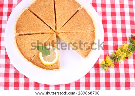 Round lemon cake, cut into slices. Delicious lemon cake. Pastries, patisserie, cafeteria. Pie and lemon. Dried lavender and pie on the table. Food, pastries.