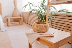 round little storage basket and natural beige towel folded on wooden table in the bathroom. the elements of bathroom decor using natural materials. Minimalism in renovation