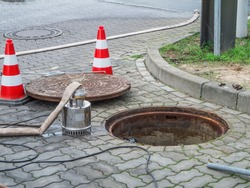 Round manhole cover next to a water meter shaft in Berlin with a pump, water hose and shut-off pylons in front of it.