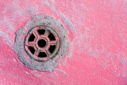 Round manhole on concrete drain system cover. Urban sewer background. Metal drain cover texture. Empty copy space industrial background. Red paint pavement.