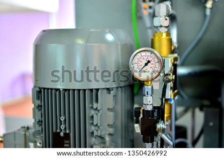 Round mechanical pressure gauges against the backdrop of an industrial electric motor. Traditional precise instrument for measuring pressure #1350426992
