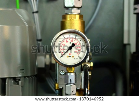 Round mechanical pressure gauges against the backdrop of an industrial electric motor. Traditional precise instrument for measuring pressure #1370146952