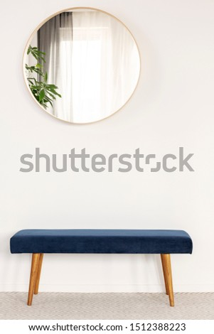 Round mirror in wooden frame on empty white wall of bright living room interior #1512388223
