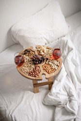 Round oak compartment dish or pick-nick table with nuts and dry fruits with glasses of rose wine on white bed in the weekend. Minimalistic colors and composition. Holiday or weekend concept.