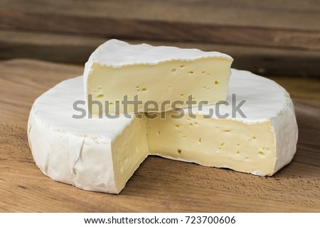 Round of Camembert cheese brie with triangle cut out placed on top .