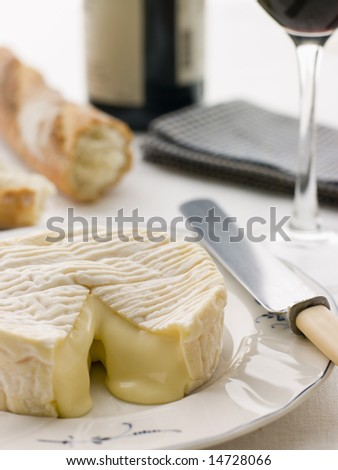 Round of camembert cheese with French stick and Red Wine