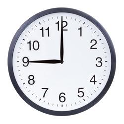 Round office clock showing nine o'clock isolated on white background