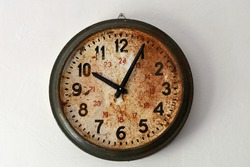 Round old clock with rust on clockface. Arabic numerals