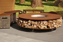 Round Patio Iron Fire Pit Table For Outdoor Leisure Party. Steel Rounded Fire Pit With Grill Top On Backyard Party Place. Grill Appliance And Fireplace On The Back Yard Lawn.