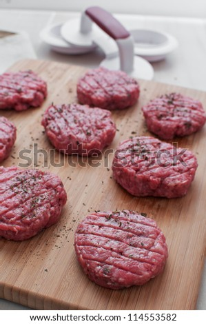 Round patties from ground beef before cooking vertical