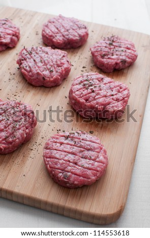 Round patties or chops from raw ground beef cooking vertical