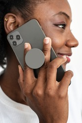 Round phone grip behind the mobile with African American woman talking on the phone