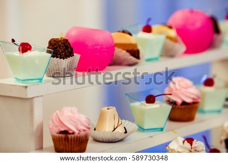 Round pink candles stand between cupcakes and cold desserts on white shelves #589730348