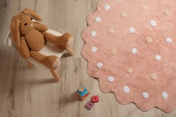 Round pink rug with polka dot pattern and toys on wooden floor in baby's room, above view