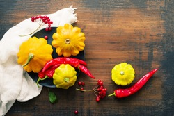 Round plate with yellow squash, red hot pepper and viburnum berries on an old wooden brown surface, top view, copy space. Autumn or Thanksgiving background.