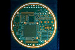 Round printed circuit board. Printed circuit board with luminous elements. Round PCB. PCB on a dark background. Concept - production of printed circuit boards. PCB as a symbol of computer technology