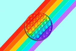 Round rainbow kids toy antistress pop it or simple dimple on a blue background with color stripes
