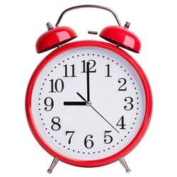 Round red alarm clock shows exactly nine o'clock