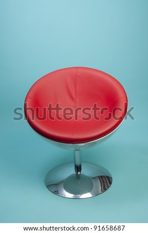 Round Red Retro Chair with chrome Pedestal on blue background