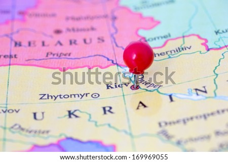 Round red thumb tack pinched through city of Kiev on Ukraine map. Part of collection covering all major capitals of Europe.