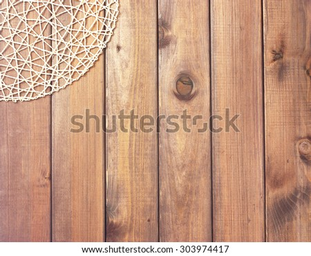 Round rope napkin or stand on a wooden rustic table. To create a collage with food. View from top.