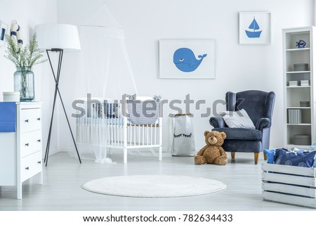 Round rug in white interior of cozy kid bedroom with oversize lamp and white crib with veil