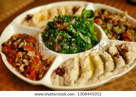 Round sectional partition plate with hummus, salad and other snacks in an Asian restaurant. Beijing, China. #1308441052