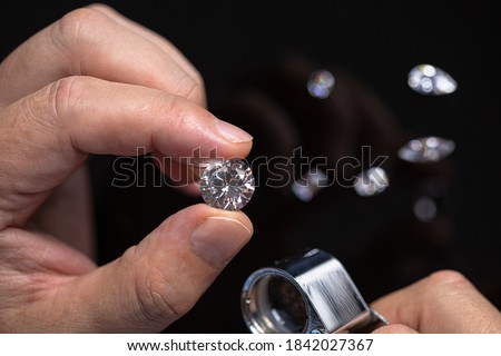 Round shape diamond in hands of jeweller. Man jeweller examines a diamond. Gem grading and checking. Diamond business.