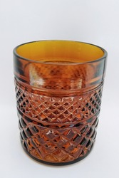 round shape of colourful old brown glass closeup .it looks old and traditional with line and crisscross like a wicker pattern as a transparent  pot or vase for vintage decoration