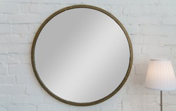 Round shape vintage golden frame mirror on white brick wall