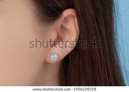 Round silver earrings on the ear of a well-groomed lady on a blue background Foto stock ©