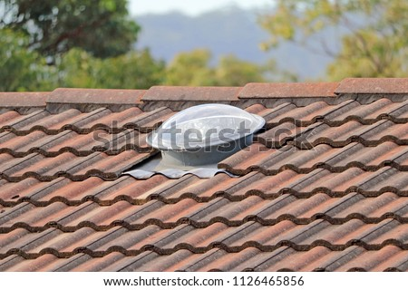 Round skylight on tiled roof