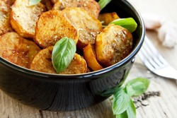 Round spicy baked potatoes with condiments and basil leaves,selective focus