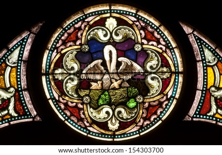 Round stained glass window depicting Christian legend of pelican-in-her-piety symbol