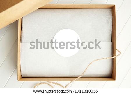 Round sticker mockup, circle white adhesive label in brown gift box.