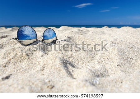 Round sunglasses with mirror reflection of sky in white sand on sunny summer beach.