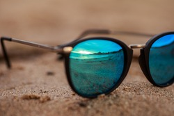 Round sunglasses with mirror reflection on the sand on sunny summer beach. Travel vacations concept.