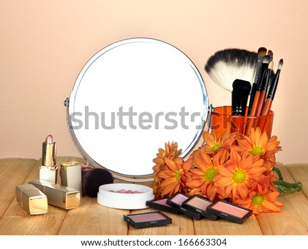 Round table mirror with cosmetics on table on beige background