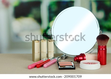 Round table mirror with cosmetics on table on bright background
