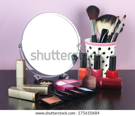 Round table mirror with cosmetics on table on violet background
