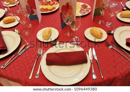 Round tables prepared in red for the celebration of a business lunch during a businessmen meeting #1096449380