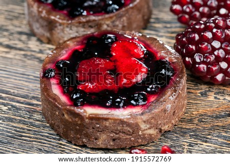 round tartlet with strawberries and blueberries in butter cream, baked tartlet dessert, chocolate tartlet with fruit and berry filling