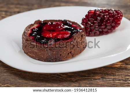 round tartlet with strawberries and blueberries in butter cream, baked tartlet dessert, chocolate tartlet with fruit and berry filling, closeup