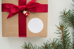 Round thank you sticker mockup for Christmas gift, circle adhesive label on kraft paper box and red ribbon.