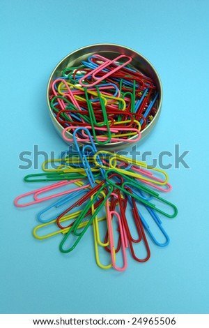 Round Tin with colorful paperclips spilling out on blue background